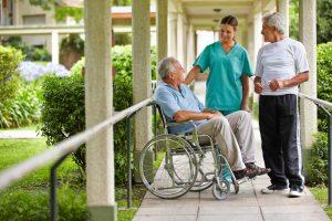 Two elderly men talking to a nurse