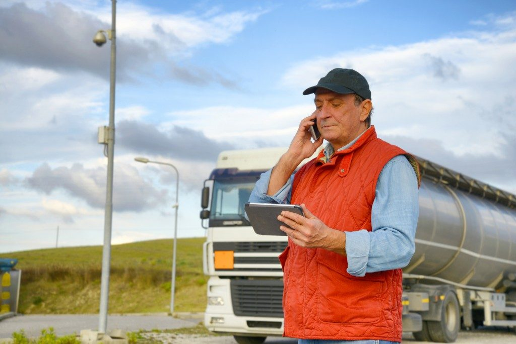 Man using phone next to truck