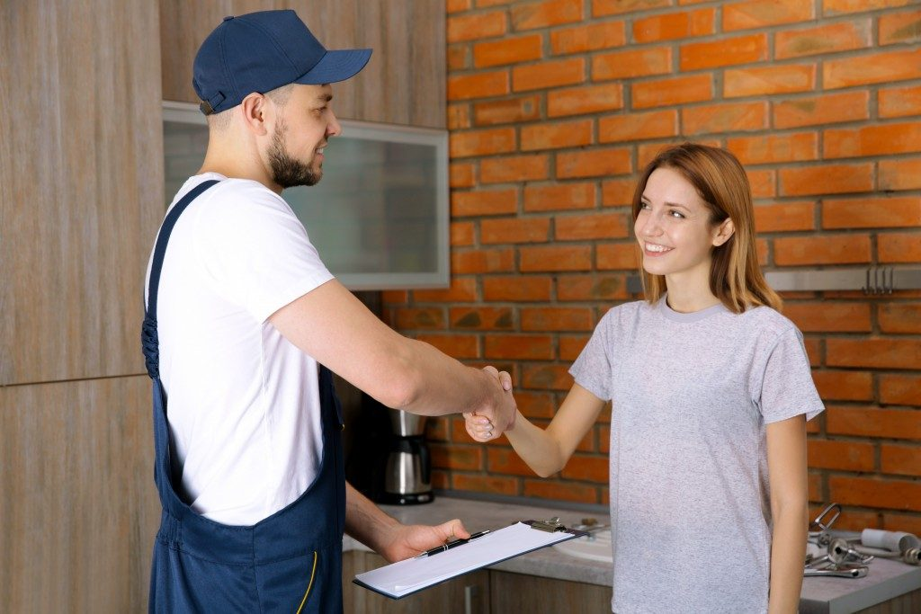 Plumber shaking hands with the client