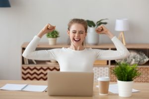 a happy woman using a laptop