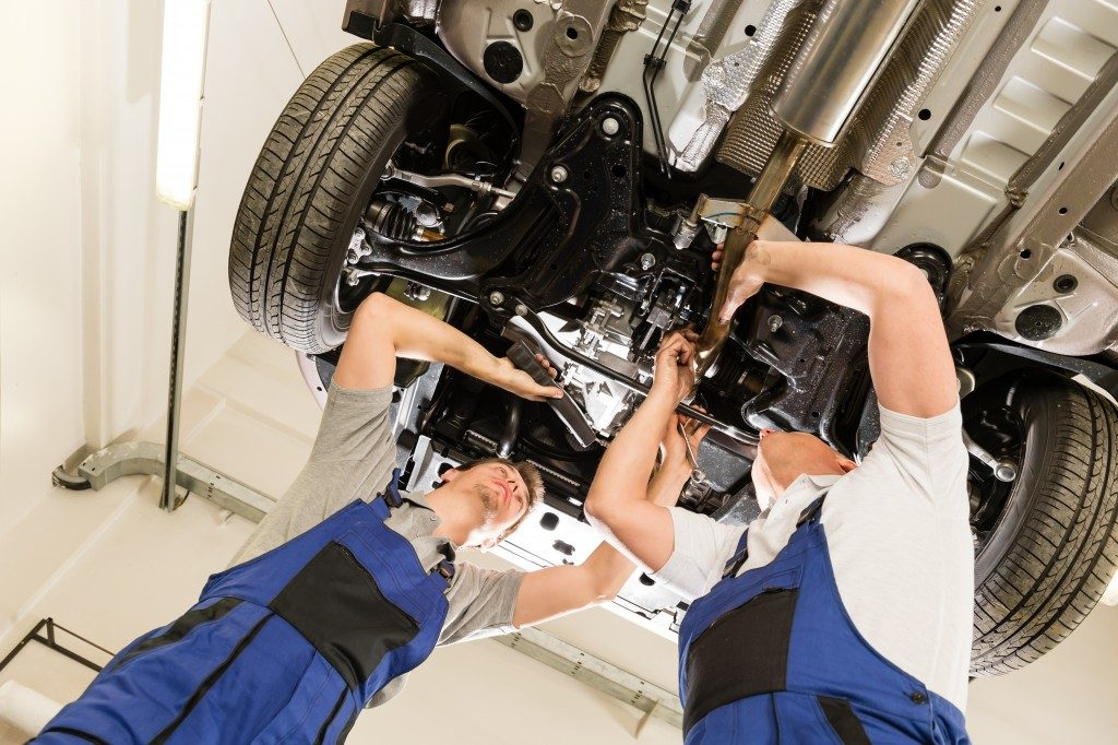 men fixing car engine