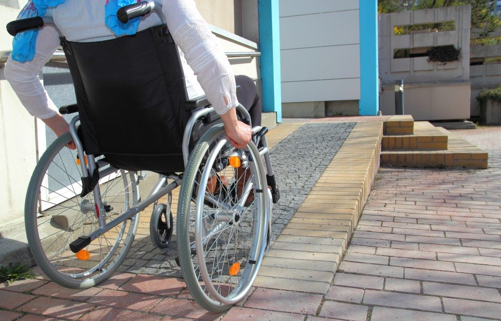 person in a wheelchair going up the ramp