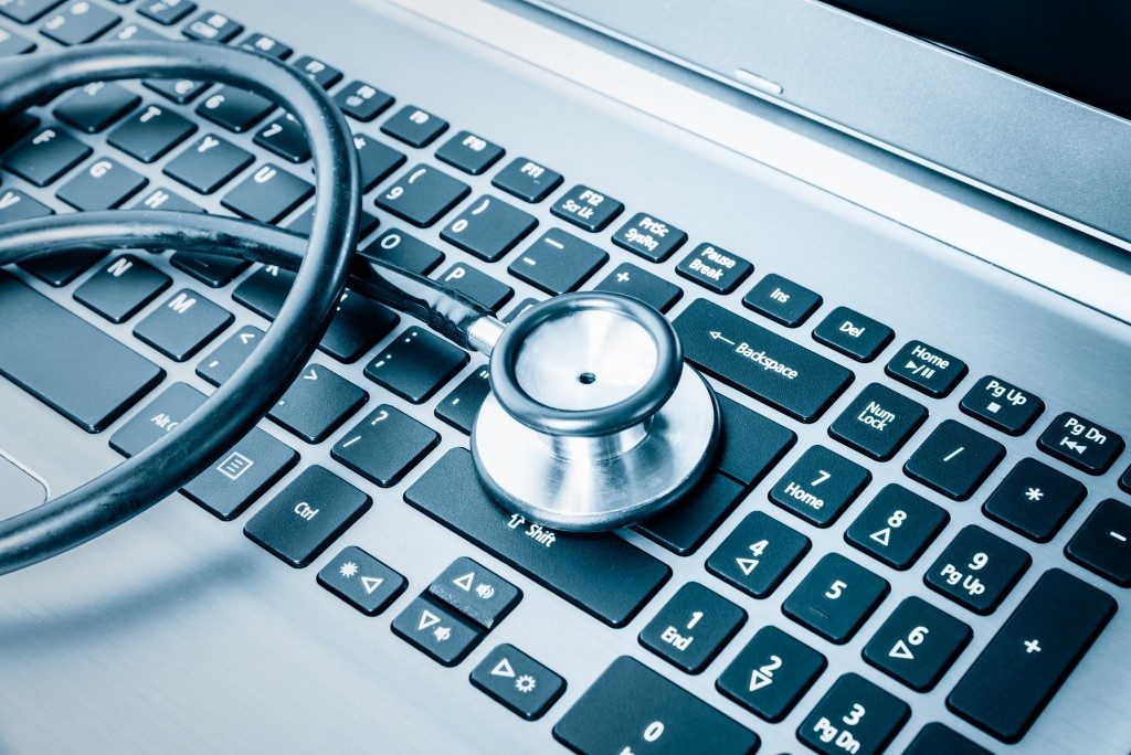 Computer system health or auditing - Stethoscope over a computer keyboard toned in blue