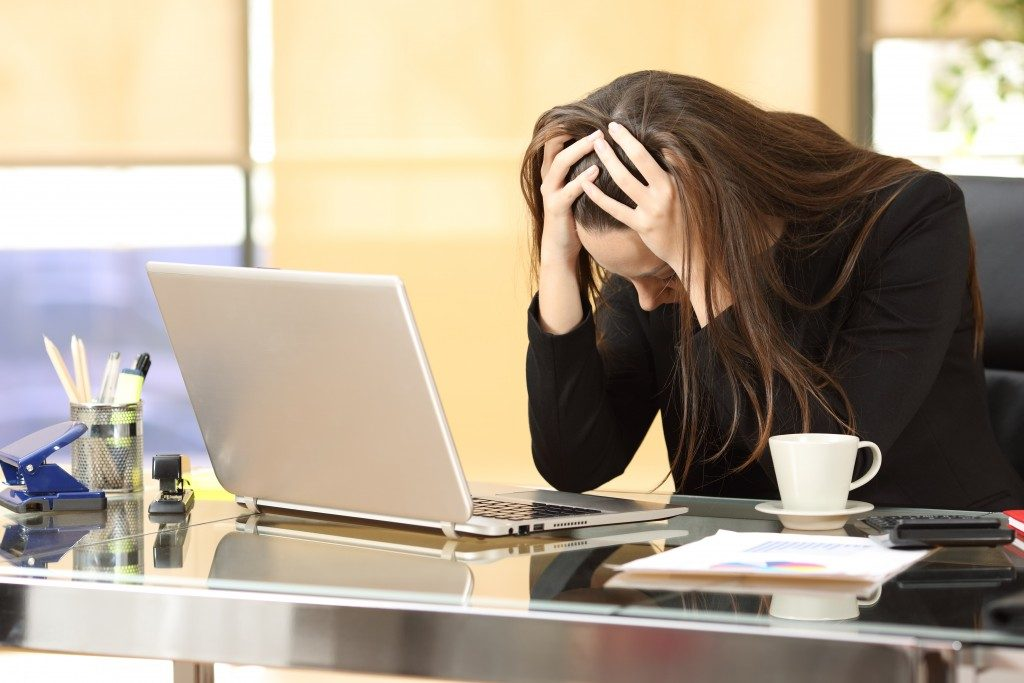 Businesswoman in front of a laptop with her hands in the head at office
