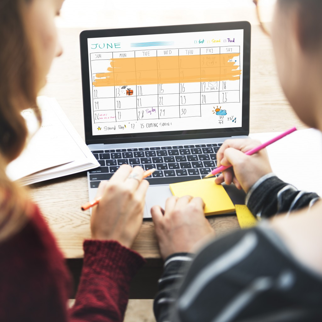 Two people going through calendar in laptop
