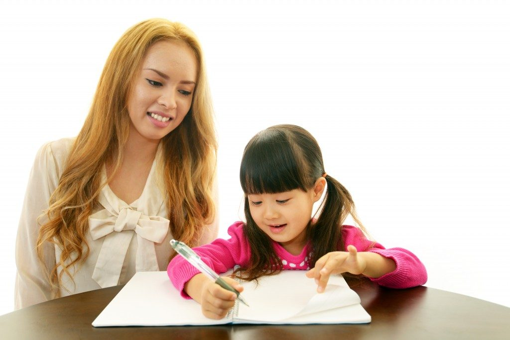 Little girl studying English with teacher