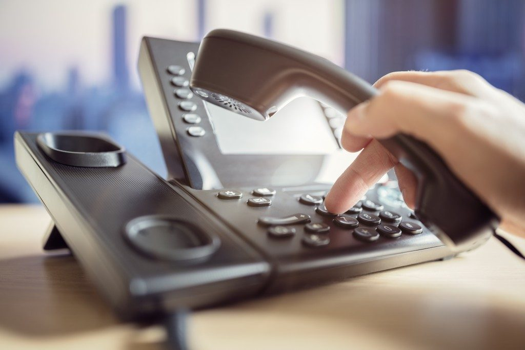 person dialing on a voip phone
