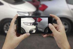 person taking photo of car's damages