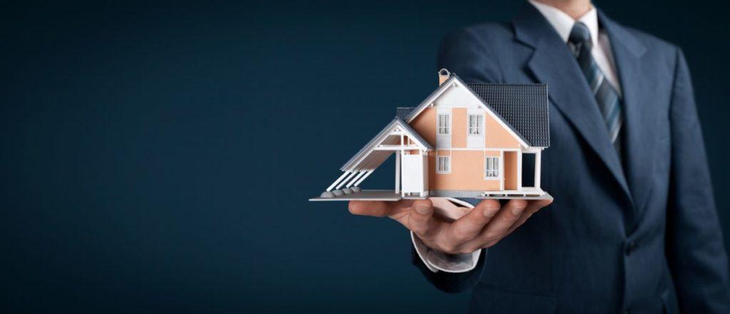 man holding miniature house