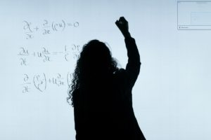 silhouette of a woman writing on a whiteboard