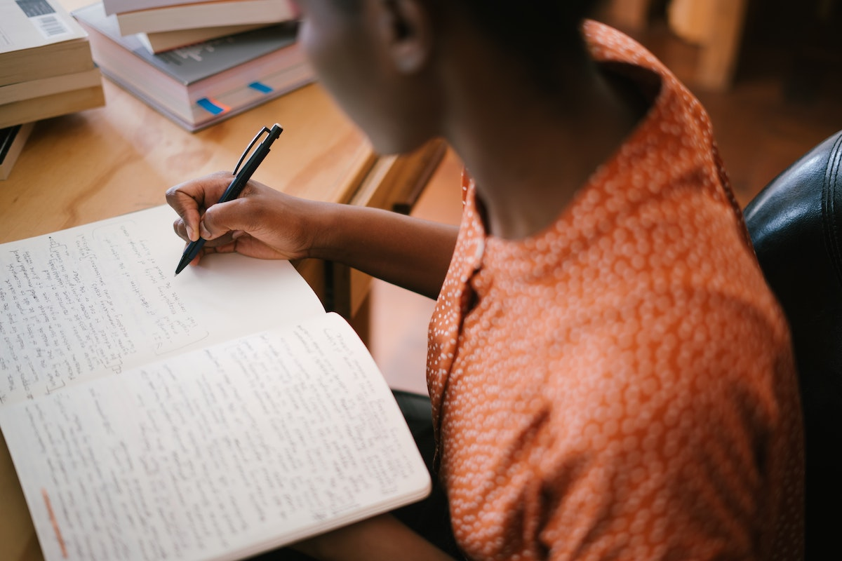 woman writing on a notebook